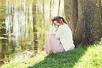 Thoughtful young woman sitting alone in woods wearing a summer dress