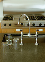 A large kitchen sink on a central island set into a durable water-resistant work surface has a set of old-fashioned taps