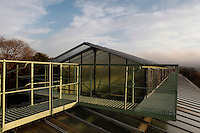 Roof of the Tropical Rainforest Glasshouse (formerly Le Jardin d'Hiver or Winter Gardens), 1936, René Berger, Jardin des Plantes, Museum National d'Histoire Naturelle, Paris, France. Low angle view showing walkways around the glass and metal roof structure beneath a cloudy sky.