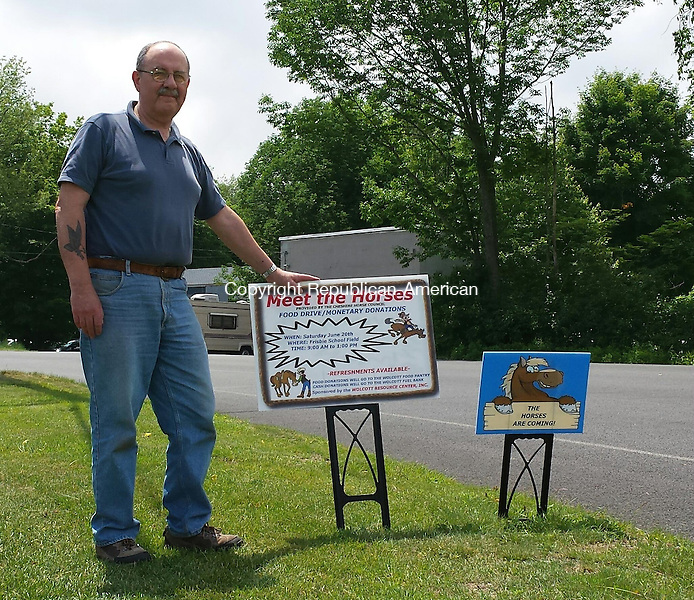 "WOLCOTT, CT - June 9, 2015 - 060915AL02 - Joe Discepolo, a volunteer with the Wolcott Resource Center, holds a sign advertising a 'Meet the Horses' food drive and fundraiser from 9 a.m. to 1 p.m. June 20 on the Frisbie School field. The organization, which runs the Wolcott Food Pantry, has placed signs that say ""The Horses are Coming"" throughout town."