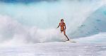 A surfer rides a wave at Ehukai Beach (Banzai Pipeline) on the Northshore of Oahu, Hawaii.