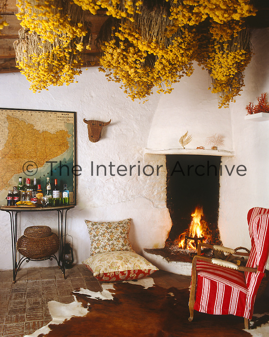 Local flowers have been hung to dry around the corner fireplace in this simple living room