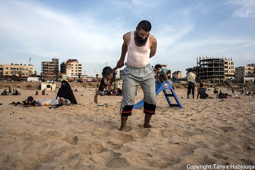 A father takes his son for a spin, playing with his children on a friday afternoon in Gaza on the beach.