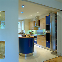Navy blue kitchen units combined with a creamy limestone floor balance the Ying and Yang of this area.