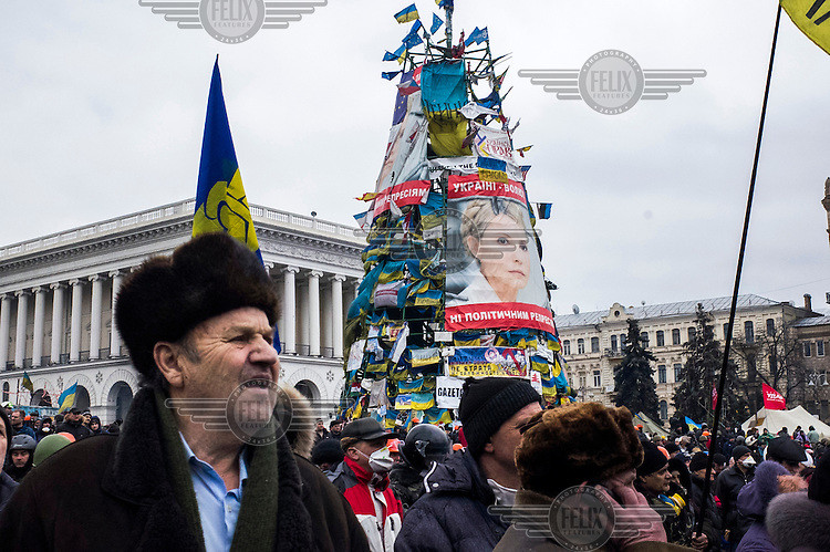 Protesters stand next to a 'christmas tree' adorned in posters and images of Yulia Tymoshenko, the jailed opposition leader, on Maidan Nezalezhnosti (Independence Square), renamed EuroMaidan by protesters since November 2013. Protests against the government of President Viktor Yanukovych were sparked on 21 November 2014 by the Ukrainian government's decision to suspend preparations for the signing of an association agreement with the European Union that would have increased trade with the EU. Some believe that the U-turn came about as a result of pressure from President Putin of Russia who wants Ukraine to join a customs union with itself, Kazakhstan and Belarus. Russia offered 15 billion dollars of soft loans and reduced price gas to Ukraine at the same time as discussions with the EU were taking place. After weeks of protests and a number of deaths, Prime Minister Mykola Azarov and the entire cabinet resigned. Protesters are holding out, however, for President Yanukovych to resign and continue to occupy public buildings and squares to put pressure on the president. On 18 February, after Yanukovych's party scuppered a move to change the constitution to reduce the powers of the president, renewed fighting between protesters and police broke out and had cost the lives of around 80 people by Friday 21st February.