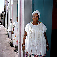 70 year old Irmana Joselita (front) has been a member of the Irmandada da Boa Morte (Sisterhood of the Good Death) for 18 years. The Sisterhood began as a bank in 1823, founded by freed slaves, to finance the freedom of men, women and children still bonded by slavery. The community, which is still made up of the descendents of slaves, is one of the oldest and most respected worship groups for Candomble, the major African-based religion in Brazil. The sisterhood practices a syncretised worship that combines Candomble, Catholicism and Islamic elements. Thanks to their microcredit scheme, and the two hundred religious events they organise throughout the year, the Sisterhood have achieved a central role in regional society, preserving some of the traditional African values that slavery brought to Brazil.