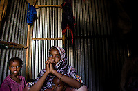 "Siida Noor Ahmed, 29 years old. Siida fled Mogadishu, Somalia, with 7 of her ten children and arrived  at State House IDP camp in January 2009. Her husband and 3 of her children disappeared during recent fighting in Mogadishu. .At state house she is being helped by long term resident Koos Aw Dahir with  rent, food and childcare. Koos was one of the original  residents of state house and recognized somthing of her own struggle in Siida's story..According to Siida ""I came here to get peace and to keep my children.  Three of my children went to school one day in Mogadishu.  There was fighting at the school so they ran away and got lost.  I don't know if they're alive or dead.  It's part of my body which is missing.  If only I could be told my children are dead - I could give up."".  .""Nobody normal lives in Mogadishu now - they're all abnormal.  Sometimes you see people in groups - after a few minutes a section of a person is brought back in pieces.  Sometimes people bring back the head of a friend saying 'I found a head.'""..""It's luck to eat.  People go into Mogadishu in search of casual work.  Sometimes they're given a bag to carry somewhere for 20,000 Somali shillings. But the bag is a bomb.  When they reach the destination, the person who gave it to them detonates it.""..""It was very hard to leave.  I didn't know where I was going.  My problem here is a lack of food.  How do you feel when you rely on people - when you go and ask 'have you cooked?'  Imagine how that feels if you've been working before.  We feel like we're becoming a problem to the neighbours.""..""But we're happy because we have peace, people here have given us a house and the lady next door is helping me.""  ."