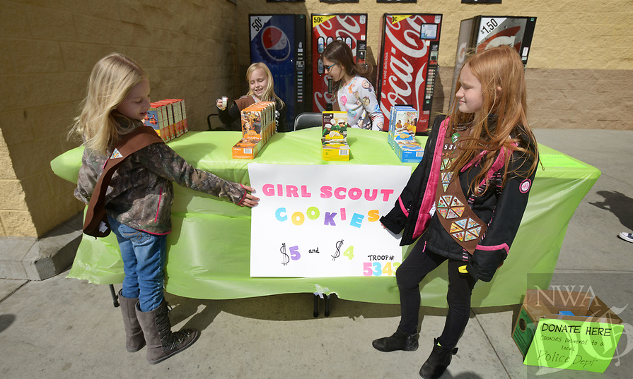 NWA Democrat-Gazette/BEN GOFF @NWABENGOFF<br /> Caroline Barnett (from left), 9, Olivia Tingley, 8, Emma Griggs, 9, and Emily Starkey, 8, tend their table Saturday, March 12, 2017, while Girl Scout Brownie Troop 5343 holds a cookie sale outside the Wal-Mart on Elm Springs Road in Springdale. The troop plans to donate $200 from the sale to the Springdale Animal Shelter and was also accepting donations to give cookies to the Springdale Police Department.