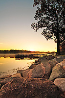 Sunrise on Hyland Lake in Bloomington, Minnesota from rocky shoreline with fishing dock and fog.
