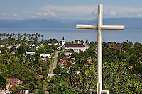 A crucifix standing sentinel above one of the main streets (leading to a newly constructed church) in largely Christian Masohi. The 1999-2002 religious war between Maluku's Christian and Muslim populations, mainly centred on Ambon Island, led to over 5000 deaths and to around 500,000 people become displaced.  Destroyed homes and offices, churches and mosques are slowly being either torn-down or renovated.  Urban centres, such as Ambon City, continue to be split along largely sectarian lines, and tensions are never far below the surface.  Riots between Christian and Muslim youths erupted in September 2011 and, most recently, June 2012, though luckily simmered down just as quickly, partly due to community leaders learning how to defuse tensions from the earlier, more devastating, conflagration.  April, 2013.  Credit: Chris Stowers/PANOS /Felix Features