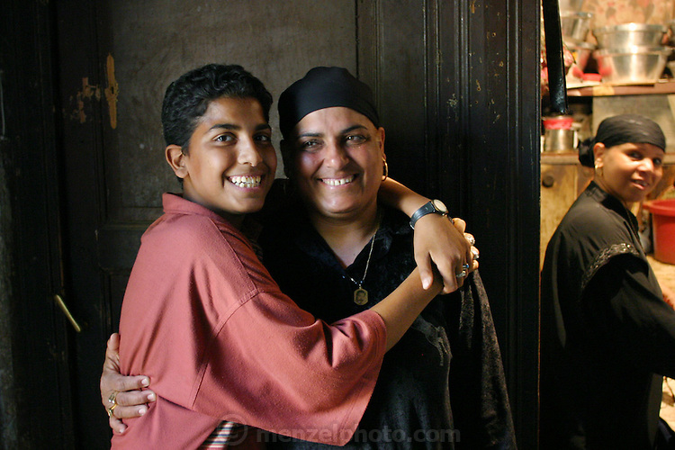 Mother and son in the small kitchen of their living space. The family is living in a large tomb in the city of the dead in Cairo, Egypt. They are acting as caretakers.