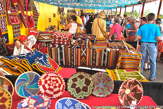 The Santa Fe International Folk Art Market attracts a huge crowd of shoppers and features a wide variety of folk artists from all over the world. Moroccan weaver Rkia Ait ElHasan relanxes for a moment surronded by colorful baskets and weavings at the July 2011 event.