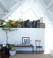 Under the angular, industrial rafters is an upstairs living area which holds a collection of luggage including pieces by Bottega Veneta, Hermes and Prada. The Scandinavian vintage table and photograph by Bruce Weber stand on a teak floor