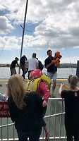 BNPS.co.uk (01202 558833)<br /> Pic: AlanDobson/BNPS<br /> <br /> The two children are handed to female passengers as Beattie helps their mother off the yacht...<br /> <br /> A dramatic video captures the moment former England striker James Beattie lept into action at the weekend to help a female sailor and her two children trapped under the Sandbanks ferry in Poole.<br /> <br /> The ex-Everton and Rangers striker leapt into action when he heard a woman shout out 'get my children off' as she feared the 25ft boat was about to sink.<br /> <br /> Mr Beattie, 38, and three other passengers jumped a barrier at the end of the small car ferry in Poole and rushed to the edge of a ramp and hauled the crying children to safety.<br /> <br /> Their shaken mother was then helped off the boat.
