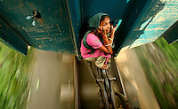 A young woman travels on the locking system of a train carriage to avoid paying the Tk 5 fare (1 USD = 72 Taka).