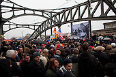 Berlin, Germany<br /> November 9, 2009<br /> <br /> Crowds look on as Chancellor Angela Merkel and former Soviet leader Mikhail Gorbachev crossed a former fortified border, the Bornholmer bridge, on Monday to cheers of &quot;Gorby! Gorby!&quot; as a throng of grateful Germans recalled the night 20 years ago that the Berlin Wall gave way to their desire for freedom and unity.<br /> <br /> Within hours of a confused announcement on Nov. 9, 1989 that East Germany was lifting travel restrictions, hundreds of people streamed into the enclave that was West Berlin, marking a pivotal moment in the collapse of communism in Europe.<br /> <br /> Merkel, who grew up in East Germany and was one of thousands to cross that night, recalled that &quot;before the joy of freedom came, many people suffered.&quot;<br /> <br /> She lauded Gorbachev, with whom she shared an umbrella amid a crush of hundreds, eager for a glimpse of the man many still consider a hero for his role in pushing reform in the Soviet Union.
