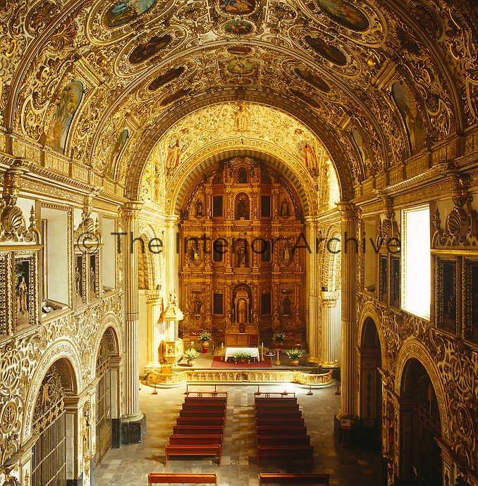 A view over the barrel-vaulted highly decorated nave of the church of Santo Domingo in Oaxaca with its wealth of baroque stucco work and inset paintings of saints and biblical scenes