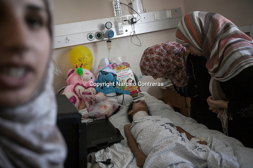 "In this Saturday, Aug. 16, 2014 photo, Maha Shaik Khalil, a 7 yo girl, barely tries to speak to her relatives as she lies helplessness on a bed in Al-Shifa hospital in Gaza City. Maha survived after an Israeli bomb targeted her family house in Shuyaja neighborhood during the ""Protective Edge"" military operation in Gaza Strip. Maha is totally paralized from neck down her body due the severe wounds at her spinal nerves. (Photo/Narciso Contreras)"