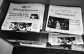 Uniontown, Pennsylvania.USA.October 23, 2004..Two newspapers on a news stand : one with a photo of Bush greeting a crowd in Penn as he campaigns for re-election and another of a funeral of a US soldier who was killed in Iraq ... being buried in another part of Penn..