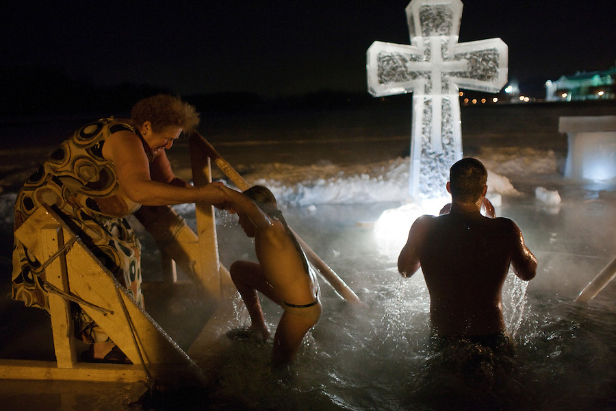 Moscow, Russia, 18/01/2011..A woman helps her grand-daughter from the water as Orthodox Christian believers celebrate Epiphany at a lake in eastern Moscow. Priests blessed the waters and followers baptised themselves by total immersion in the freezing lake in temperatures of minus 15C.