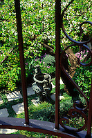 Elevated view of the front garden from the balcony onto a bronze replica urn flanked by two cupid figures