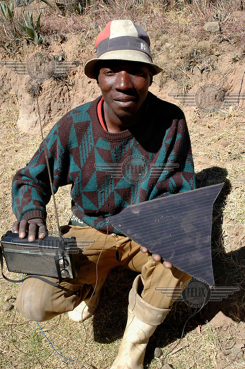 A man with his radio powered by a broken piece of Solar panel. /Felix Features
