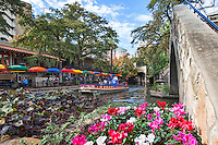 Here is another image of the San Antonio river walk cityscape in the downtown area taken near the pedestrian bridge with the lovely flower and a riverboat on it way to pick up passengers as it floats along in front ot Cafe Rio.