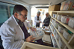 While Pharmacist Aodeshu Yanan attends to patients, Pharmacist Aodeshu Yousif sorts through boxes of drugs in the back of a van that's part of a mobile clinic visiting the village of Sharafiya, Iraq, which was flooded with displaced families when the Islamic State group took over nearby portions of the Nineveh Plains in 2014. Yanan was also displaced by ISIS. The clinic is a program of the Christian Aid Program Nohadra - Iraq (CAPNI).
