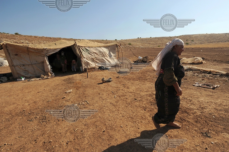 Fatma, a Bedouin woman, walks through a family encampment in Hadidyeh in the Jordan Valley. The Bedouin living here have been issued with eviction orders by Israeli authorities...