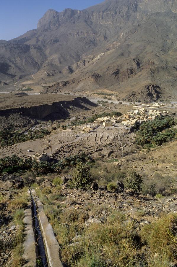Wadi Bani Kharus, Oman.  Irrigation Calan (Falaj) Carries water down Mountainside to Village and date Palms below.