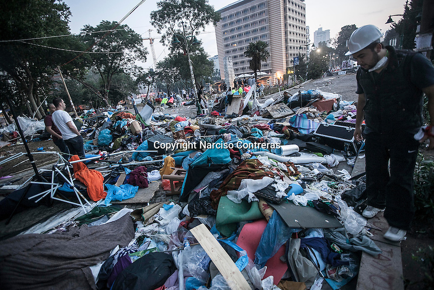 In this Sunday, Jun. 16, 2013 photo, workers clean Gezi park from the tents after anti-riot police attacked and evicted the night before the protesters camping in the park during the ongoing turmoil in Istanbul, Turkey. (Photo/Narciso Contreras).