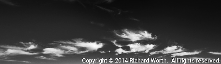 High clouds partially fill a black and white sky.  Cropped for graphic/web design