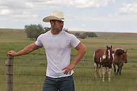 cowboy standing by a fence overlooking a horse ranch in New Mexico