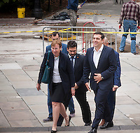 Greek Prime Minister Alexis Tsipras, right, arrives with aides at New York City Hall for a meeting with New York Mayor Bill de Blasio on Thursday, October 1, 2015. The PM and the Mayor exchanged pleasantries during a brief photo op for the press. The International Monetary Fund has been criticized for promoting its punishing austerity programs related to Greece's massive debt and weak economy.   (© Richard B. Levine)