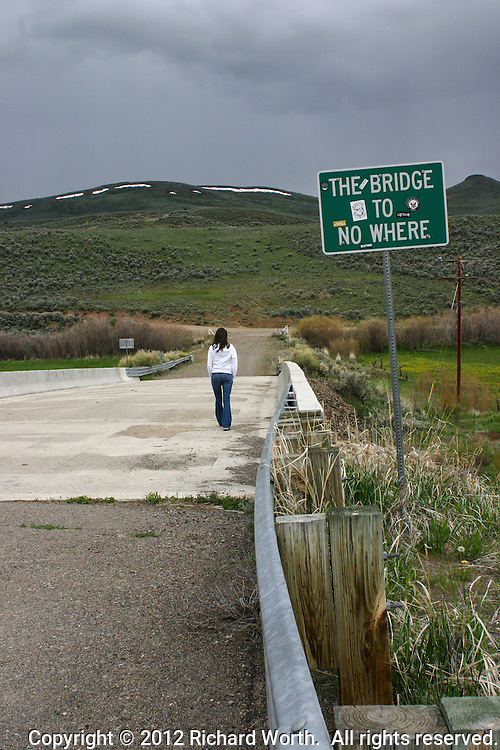 "Young woman walking away across bridge with sign ""The Bridge to No Where""."