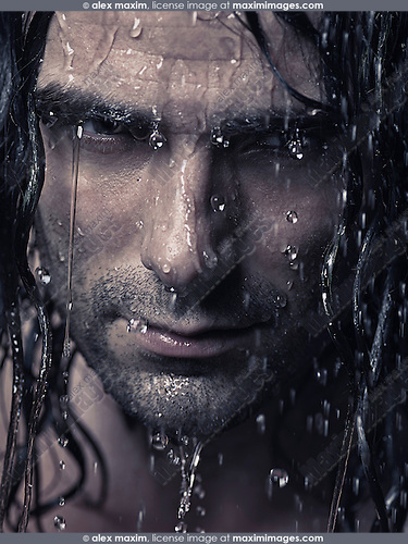 Man face with water running down it and wet long hair, artistic portrait with dramatic expression.