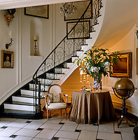 This curved staircase features a delicate wrought-iron balustrade