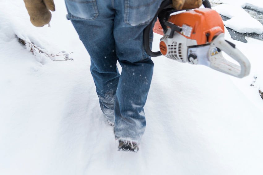 Walking in the snow with a chainsaw