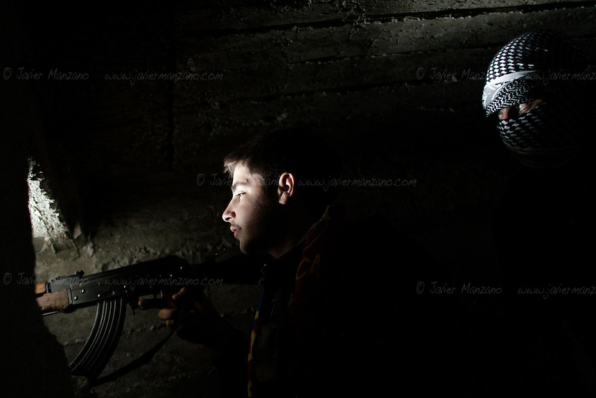Free Syria Army soldiers mount guard in their machine gun position in the Bustan Al-Basha neighborhood of Aleppo.