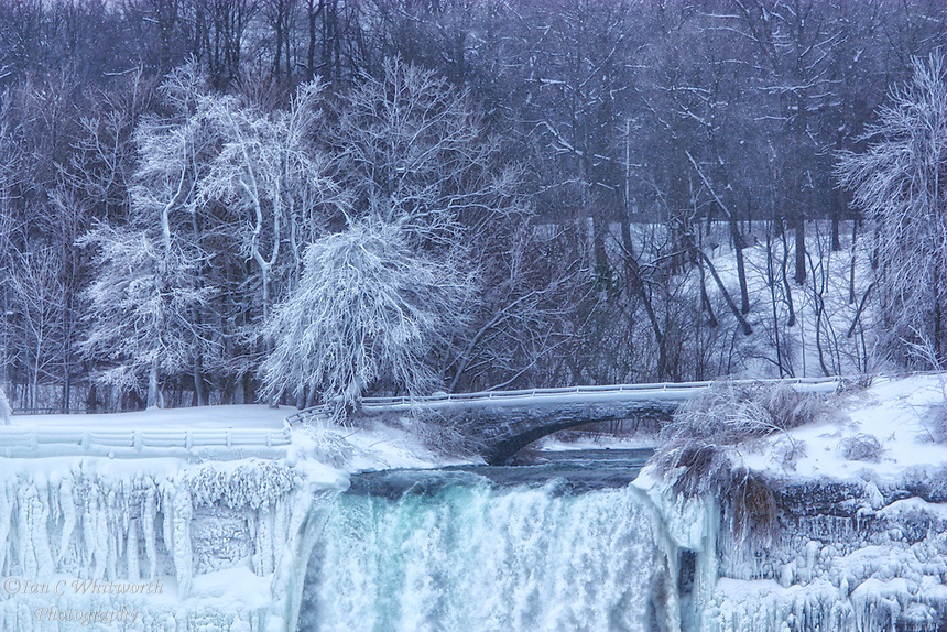 A view in the winter of a small portion of the American Falls and bridge creating a nice winter scene.