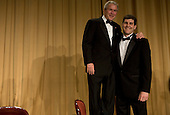 Washington, D.C. - April 26, 2008 -- United States President George W. Bush stands on a chair to shake hands with the Deborah Orin Scholarship award winner, David Rivelli, during the 2008 White House Correspondents Association Dinner. .Credit: Kristoffer Tripplaar-Pool via CNP