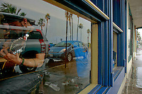John Butler tunes his guitar inside Newbreak Cafe in San Diego, California as rain pours down outside, November 30 2007. Butler and Brett Dennen played an impromptu gig at the small Cafe on Abbott Street in Ocean Beach after heavy rain forced the cancellation of the beach clean-up that they were supposed to perform at.  The clean-up was part of the Clif BAR GreenNotes Eco-Action Events series that was co-sponsored by San Diego CoastKeeper and the San Diego chapter of the Surfrider Foundation.  The show attracted a large crowd in the small cafe across the road from the beach where the clean-up was supposed to occur.