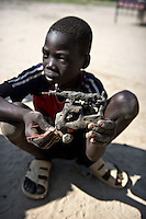 A boy plays with a hand-made toy, which resembles a military pick-up with a soldier manning a mounted gun.