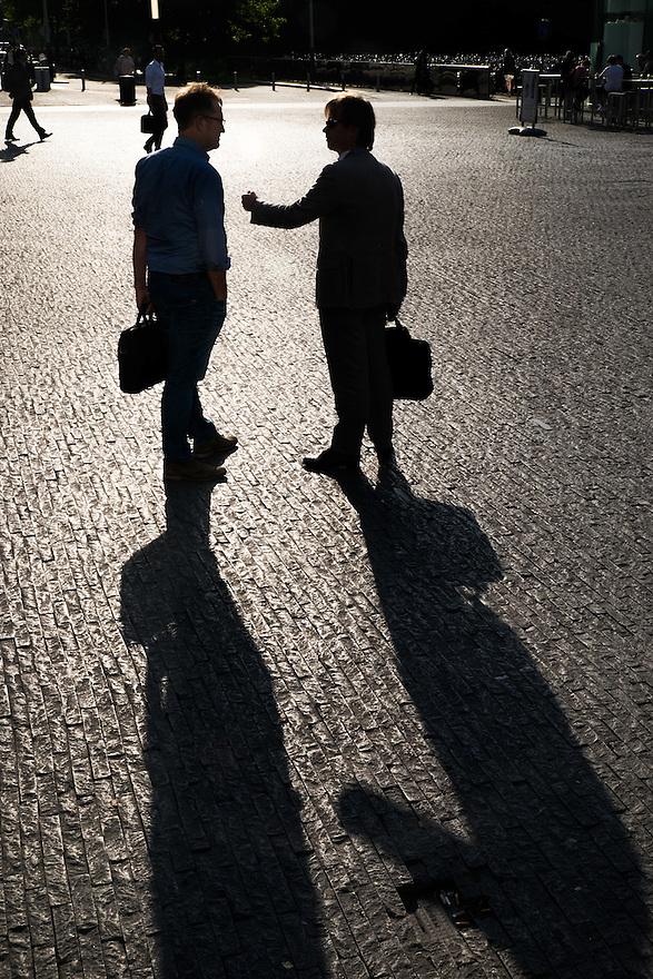 Nederland, Amsterdam, 16 juli 2015<br /> Amsterdam Zuidas. Twee mannen praten over het werk terwijl ze weglopen van het kantoorgebouw waar ze werken.<br /> <br /> Foto: Michiel Wijnbergh