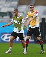 Arsenal duo Lukas Podolski and Per Mertesacker of Germany share a joke during training ahead of tomorrow's semi final vs Brazil
