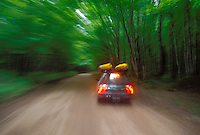 A car carrying two sea kayaks blurs through a tree covered road in Pictured Rocks National Lakeshore near Grand Marais, Mich.