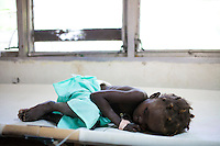 A young cholera patient sleeps on a cot at the Hospital Albert Schweitzer on Thursday, October 28, 2010 in Deschapelles, Haiti.