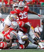 Ohio State Buckeyes linebacker Raekwon McMillan (5), defensive lineman Dre'Mont Jones (86), linebacker Jerome Baker (17) come together to bring down Tulsa Golden Hurricane running back D'Angelo Brewer (4) in the 1st quarter of their game at Ohio Stadium in Columbus, Ohio on September 10, 2016.  (Kyle Robertson / The Columbus Dispatch)