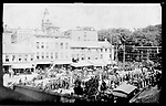 Frederick Stone Negative. Barnum's Parade, Exchange Place, 1889. In background Bauby's Bros. Fruit Store (L from R) Bolster's Hotel.