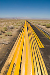 Yellow painted barrier striping used to test highway spray rig or to practice on abandoned paved roadway..Follow the yellow brick road.
